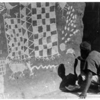 SANGA – Akundyo reproduit les dessins totémiques dans la case.