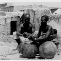 Sur la terrasse de sa maison, Ambara et sa femme font des boules d'oignon.